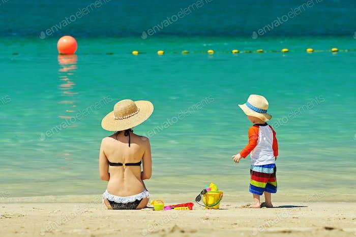 Zwei Jahre altes Kleinkind spielen mit Mutter am Strand