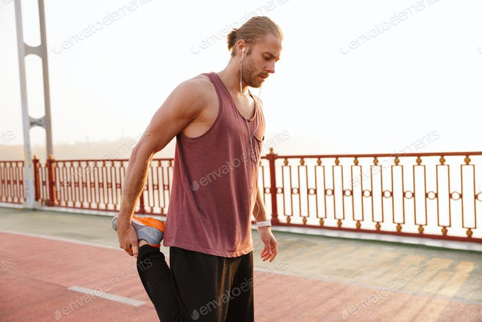 Attractive young fit sportsman working out on a bridge