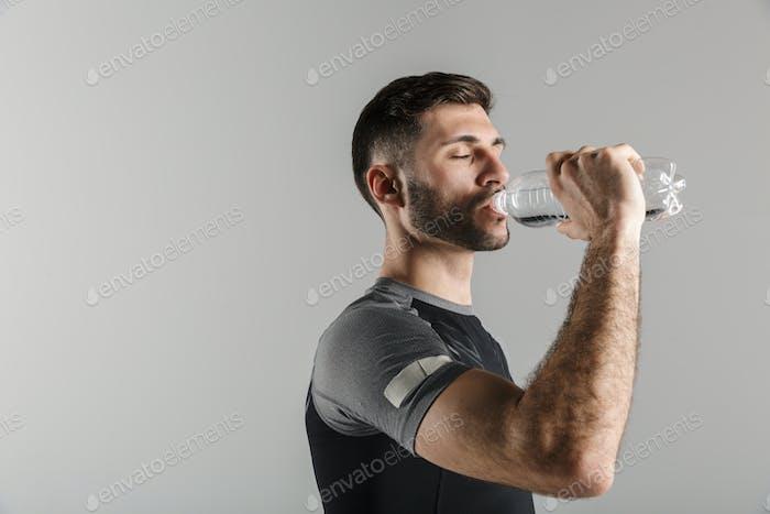 Bild eines jungen starken Mannes, der Wasser beim Arbeiten trinkt