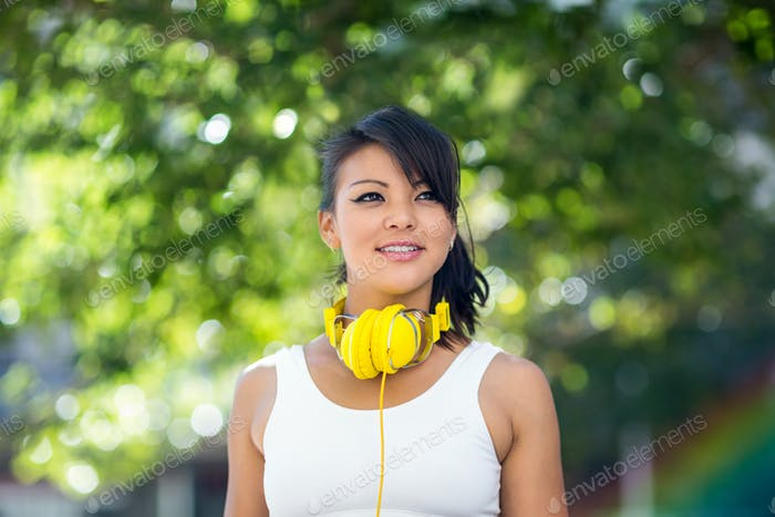 Athletic woman wearing yellow headphones in the city