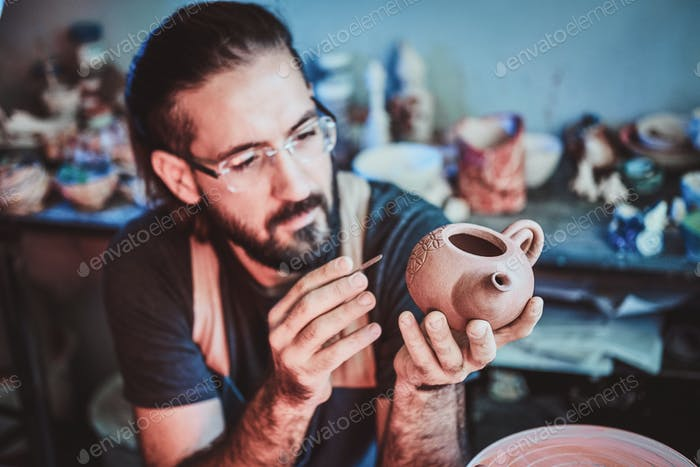 Pensive potter in glasses at his own workshop is workig on a new handmade teapot.