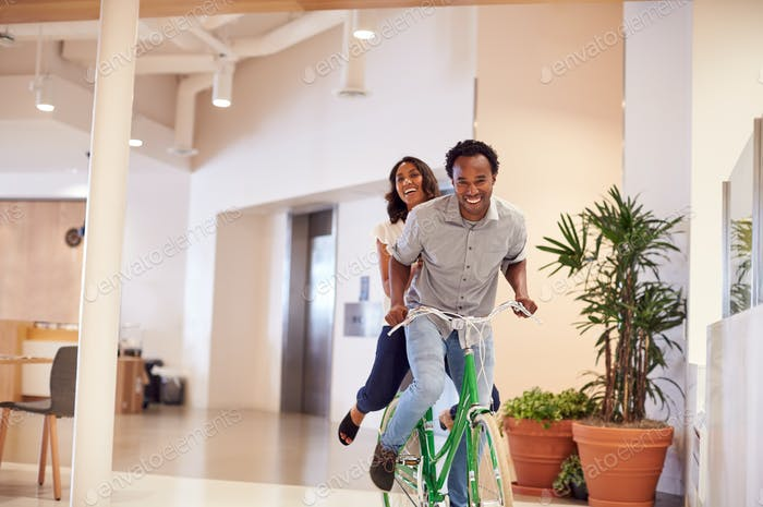 Businessman And Businesswoman Having Fun Riding Bike In Office After Cycling To Work