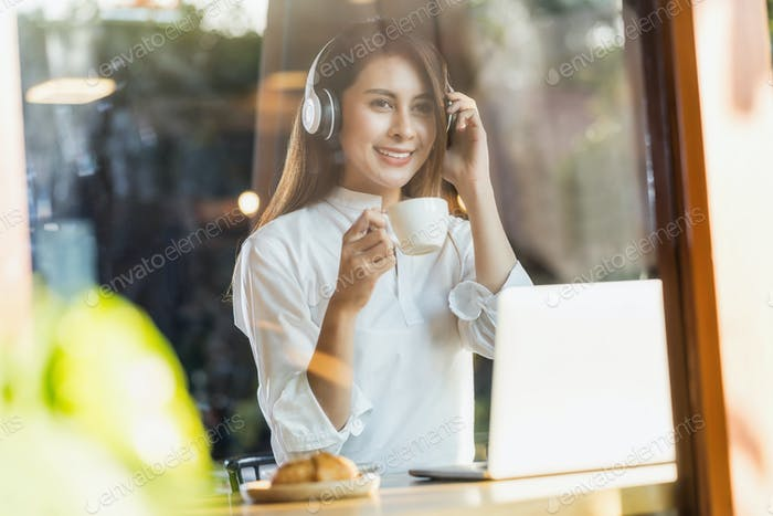 Portrait Young Asian woman holding a cup of coffee and using technology laptop