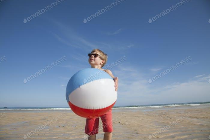 Ein Junge am Strand hält einen großen aufblasbaren Strandball.