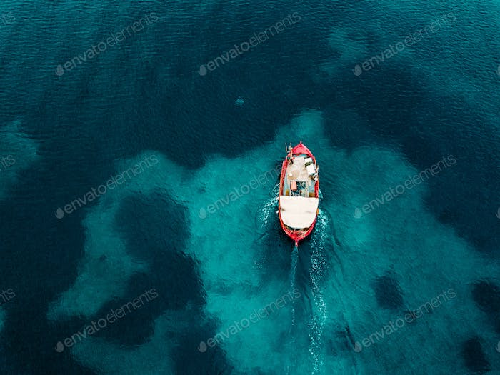 Aerial view of old fishing boat in blue sea in Greece.