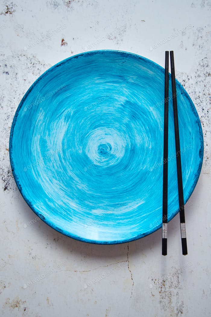 Turquoise hand painted ceramic serving plate with wooden chopsticks on side