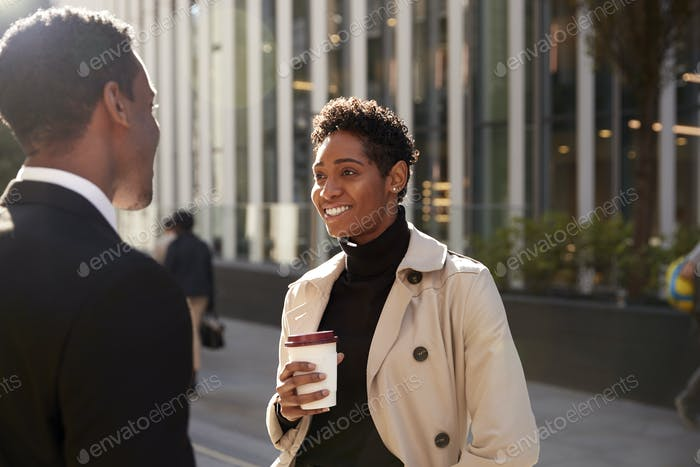 Young black businesswoman standing on the street with a takeaway coffee