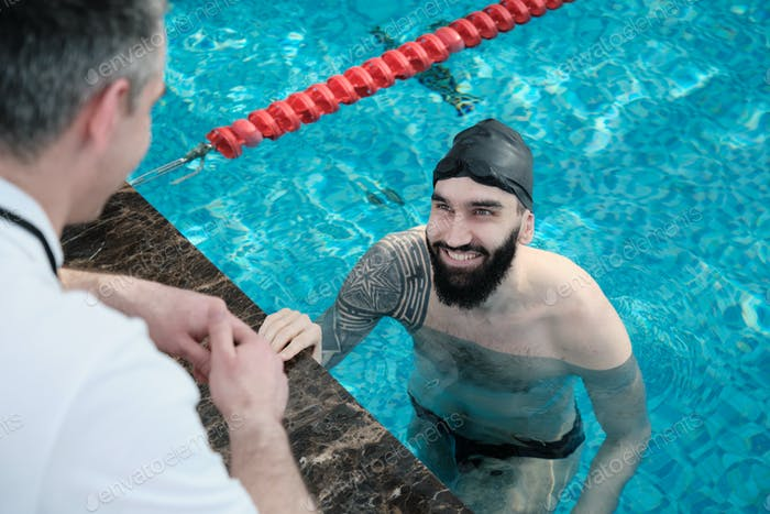 Smiling swimmer listening to coach