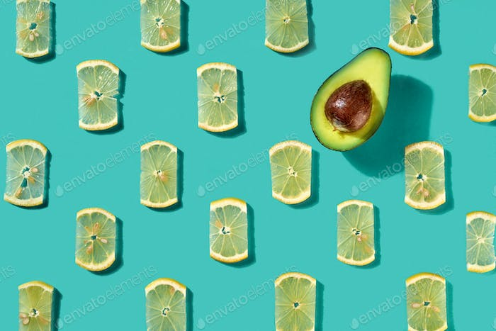 Pattern made of lemon slices and half avocado on a blue background. Food background. Flat lay
