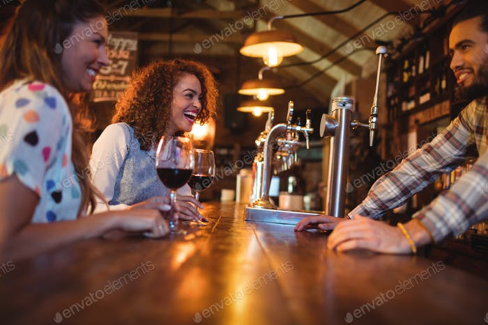 Young women interacting with bartender at counter