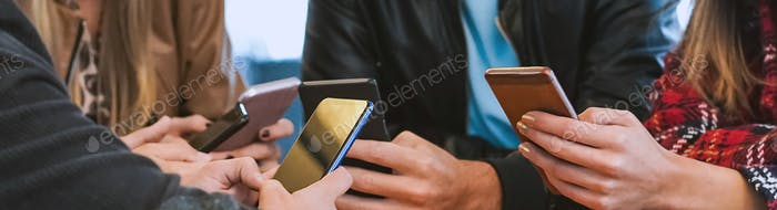 Group of people sitting around the table while holding smartphones