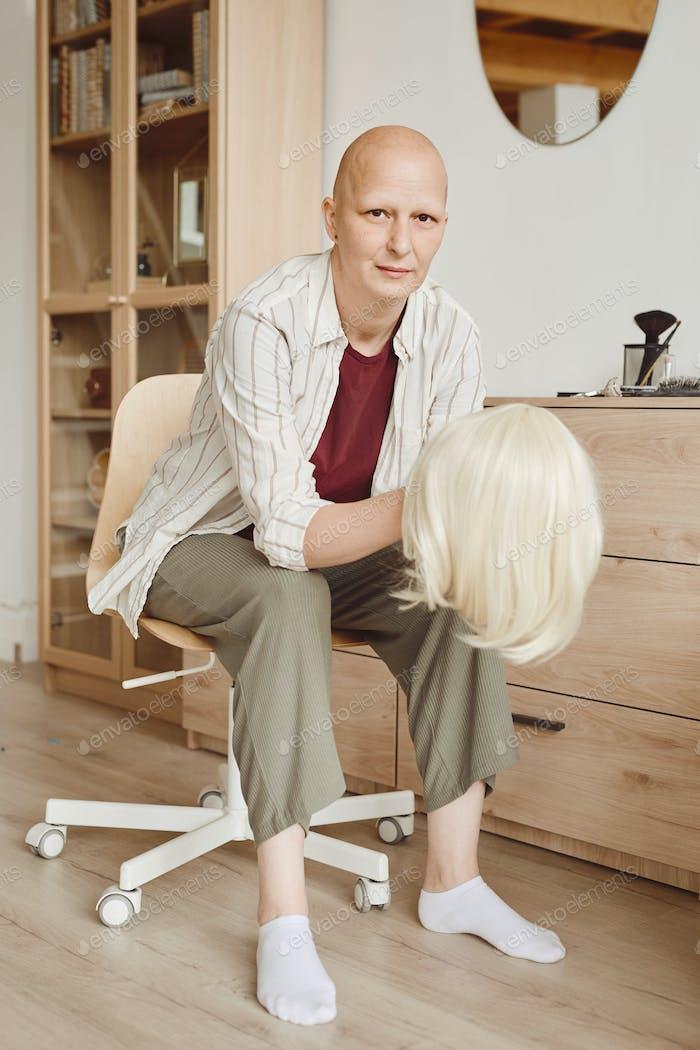 Glatze Frau hält Perücke zu Hause