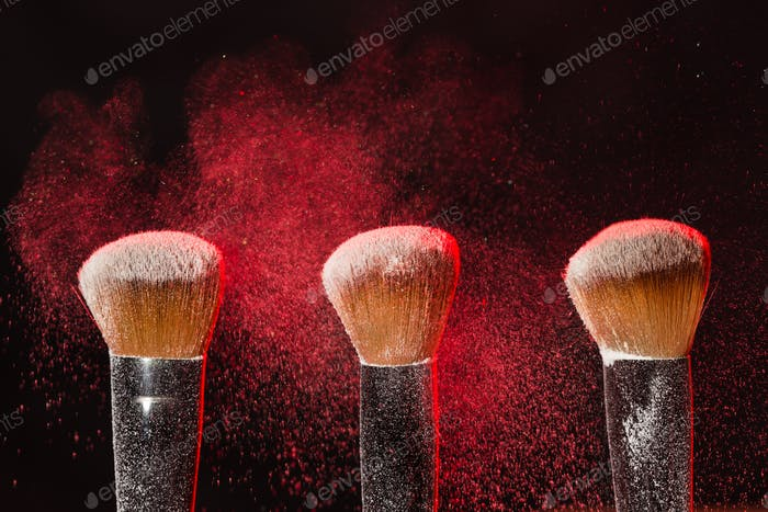 Mineral makeup and cosmetics concept - Three makeup brushes in red dust over dark background