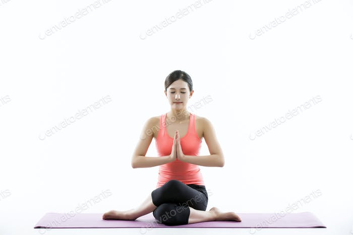Young Asian Woman Practicing Yoga on the Mat - Isolated on White
