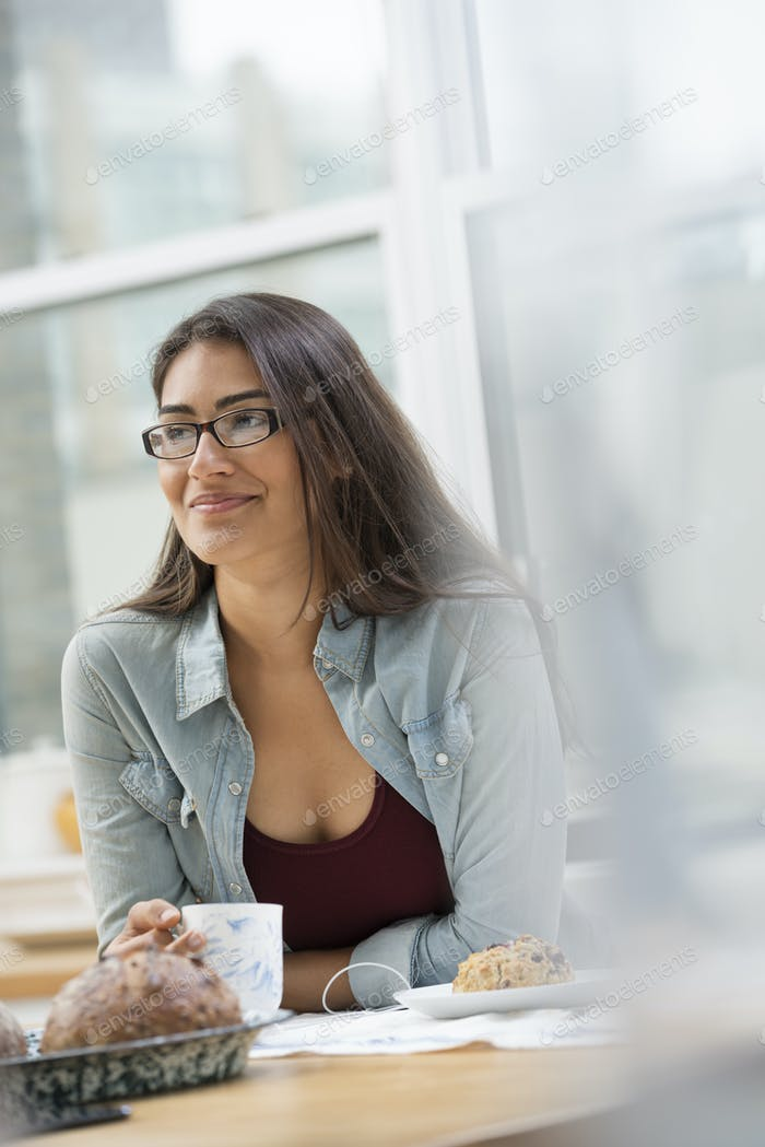 Ein Büro oder Wohnung Interieur in Eine junge Frau mit langen schwarzen Haaren, mit einer Tasse Kaffee.
