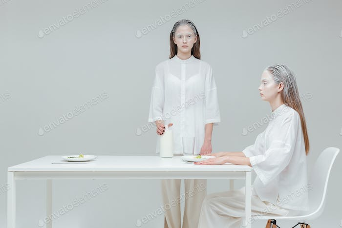 Two girls having a meal at the table