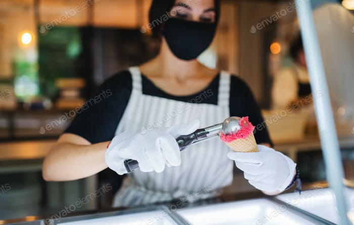 Young woman with face mask working indoors in coffee shop, serving icecream