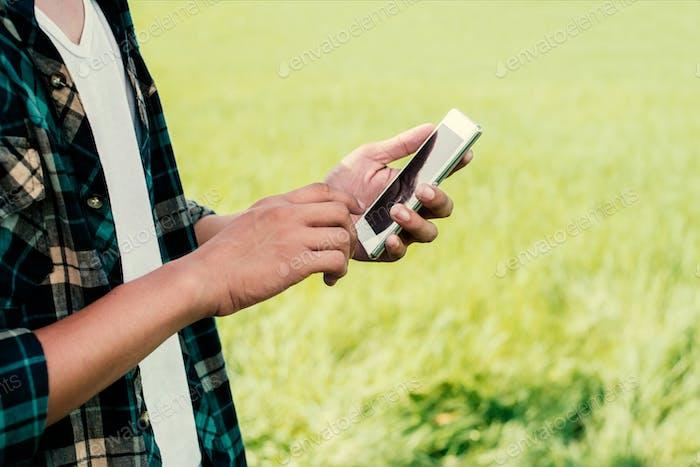 Крупным планом человек руки с помощью своего смартфона на открытом воздухе в парке.
