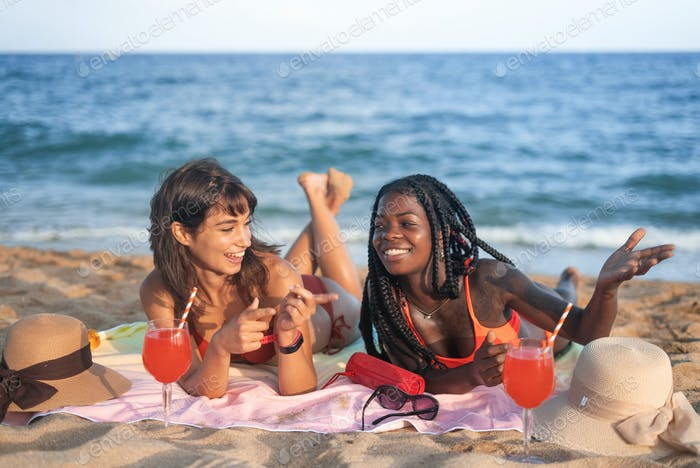 Happy diverse girlfriends chilling on beach