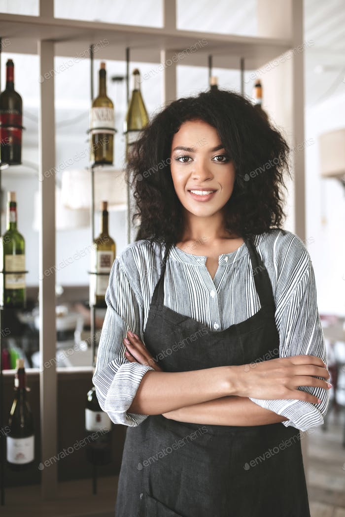 Young girl with dark curly hair standing in apron at cafe