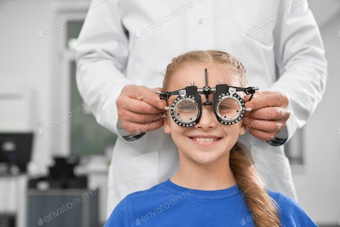 Girl in test glasses, checking eyesight in clinic