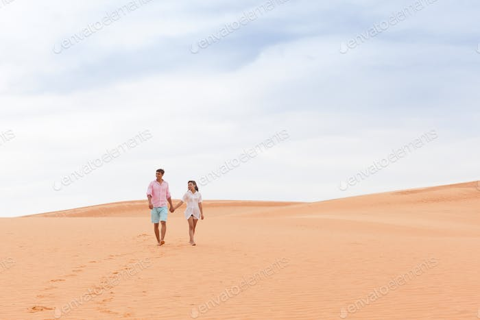 Young Man Woman Walking In Desert Couple Girl And Man Hold Hands Sand Dune Landscape