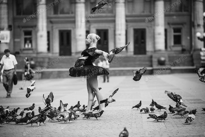 Ballerina posing among birds