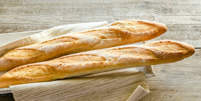 Two baguettes on the wooden tray