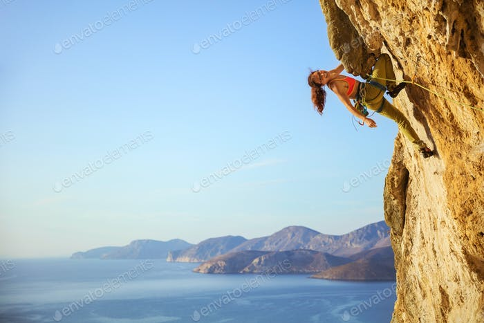 Cheerful female climber on challenging route