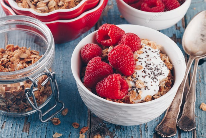 Healthy breakfast bowl granola with greek yogurt, fresh raspberries and chia seeds