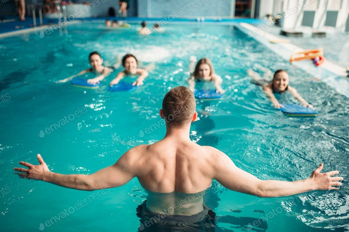 Trainer works with female group in swimming pool