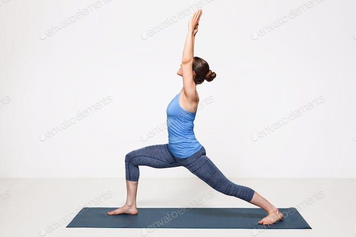 Woman practices yoga asana utthita Virabhadrasana