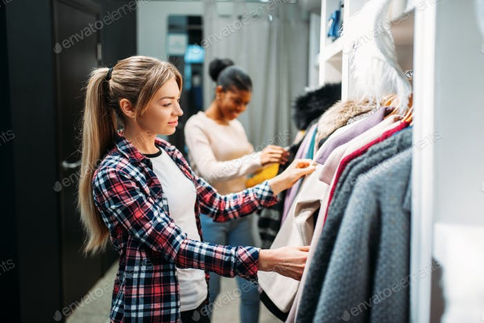 Two girlfriends choosing clothes, shopping