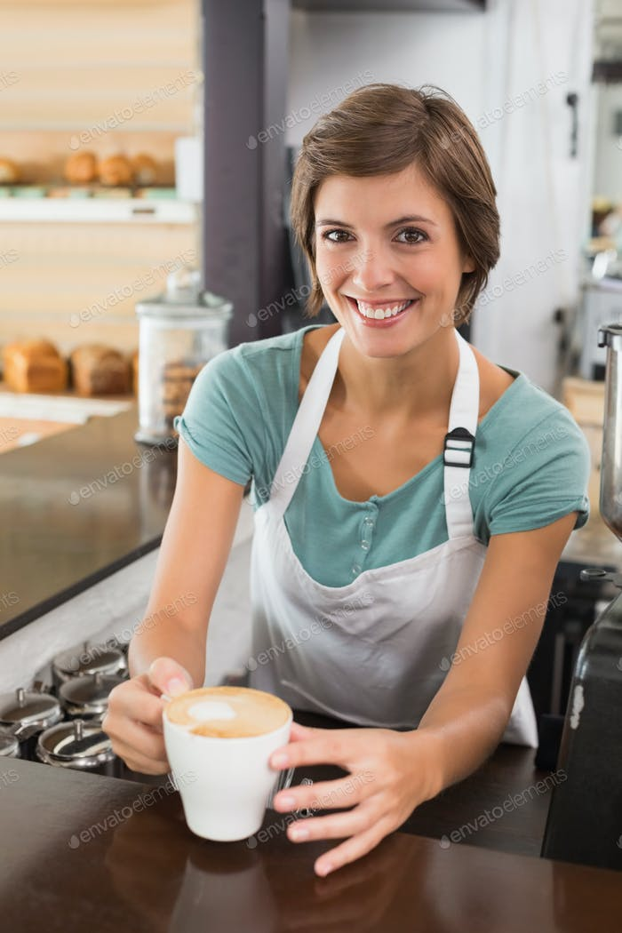 Pretty barista offering cup of coffee smiling at camera at the coffee shop