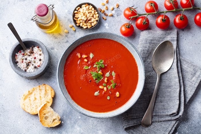 Tomato Soup with Fresh Herbs and Pine Nuts in a Bowl. Grey Stone Background. Top view.