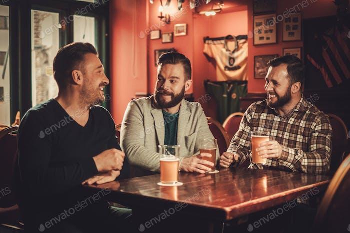 Fröhliche alte Freunde haben Spaß und trinken Bier vom Fass in der Kneipe.