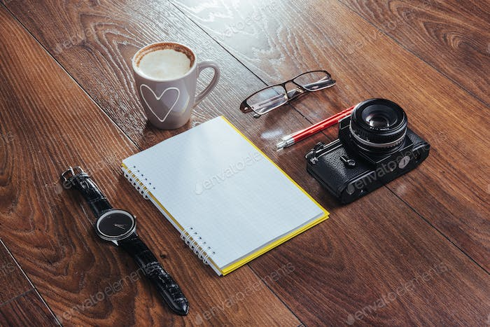 clock, camera and notebook on a brown background
