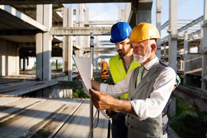 Männliche Architekten analysieren Bauplan auf der Baustelle