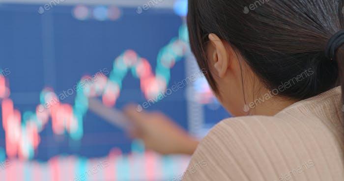 Mujer estudia los datos del mercado de valores