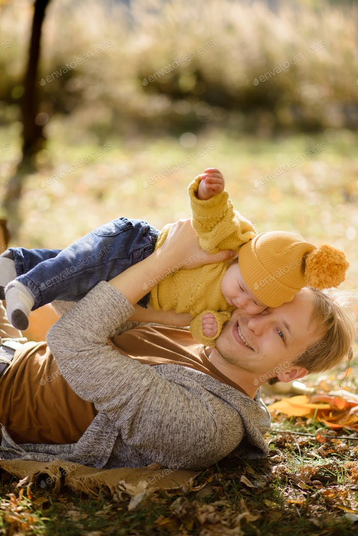 Happy father and daughter in autumn park lying on yellow leaves