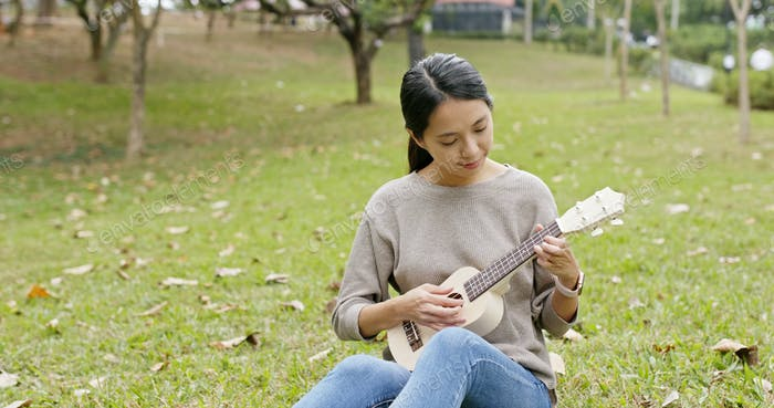 Woman play with ukulele in the park