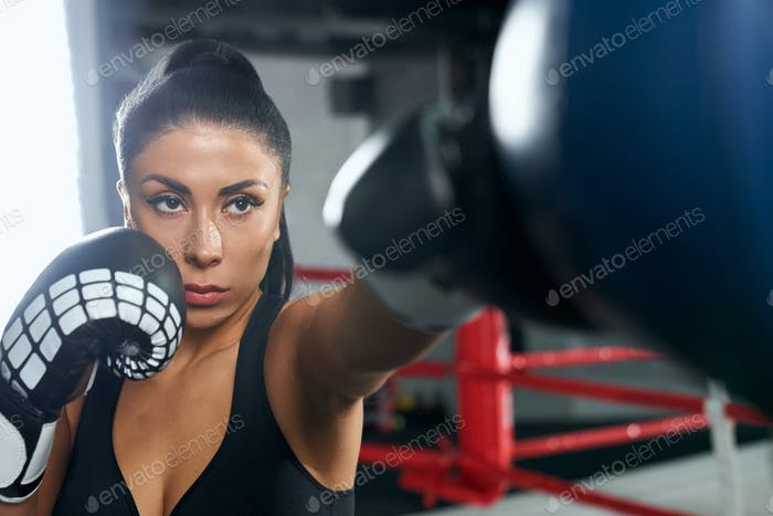 Female fighter training in boxing gloves