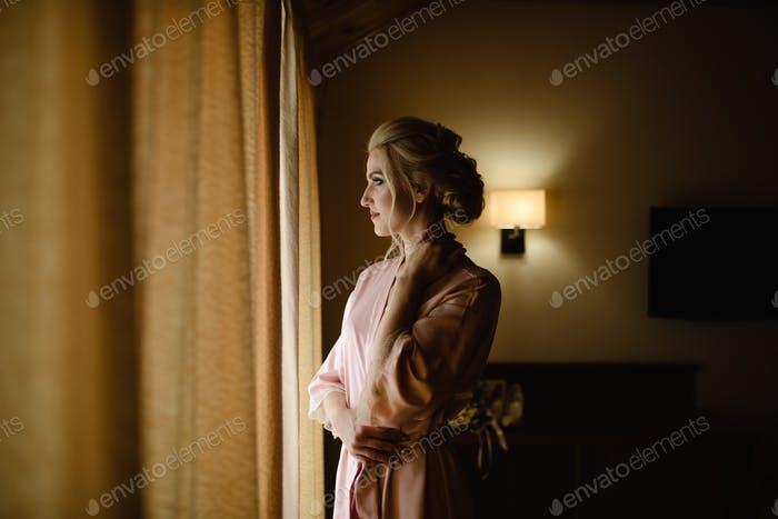 Beautiful blonde girl in a pink bathrobe looks out the window. Close-up.