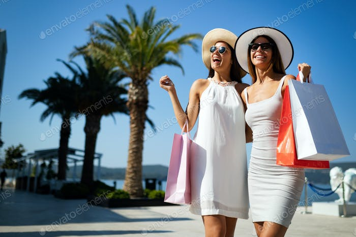 Shopping and tourism, vacation, happy, friends, people concept. Beautiful women with shopping bags