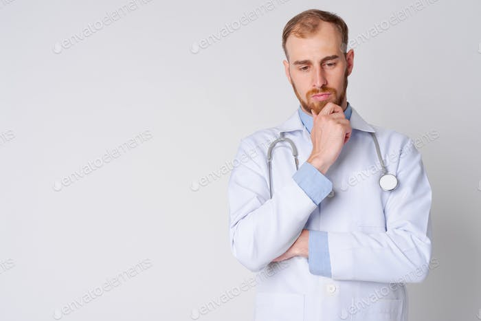 Portrait of serious young bearded man doctor thinking