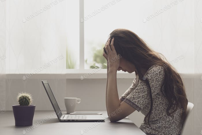 Tired stressed woman sitting at desk and connecting