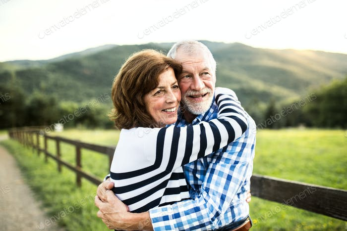 A senior couple hugging outdoors in nature.