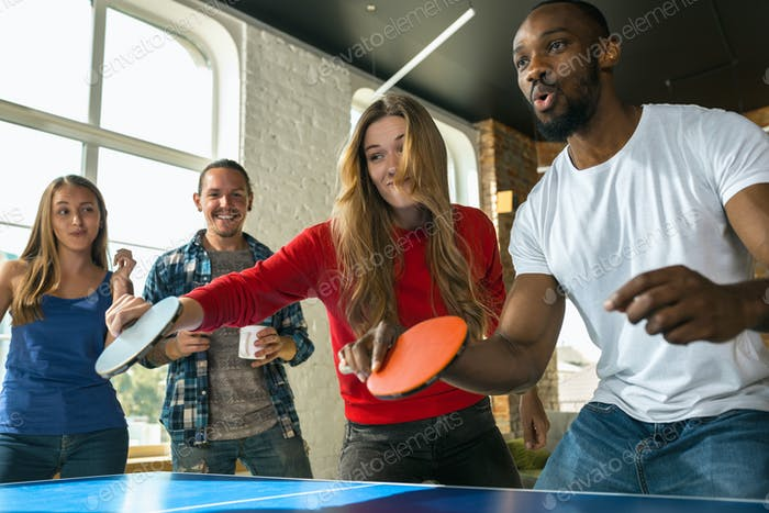 Young people playing table tennis in workplace, having fun