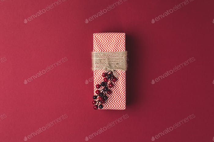 top view of wrapped and decorated christmas present on red surface