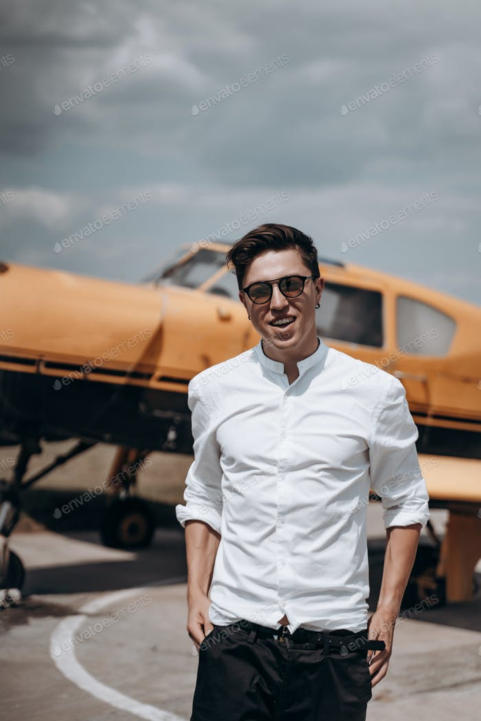 Ein Mann steht auf dem Hintergrund eines kleinen einmotorischen Flugzeugs